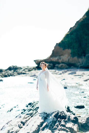 Beach wedding bride wearing real seashells and mix of blush and rose gold crystals.