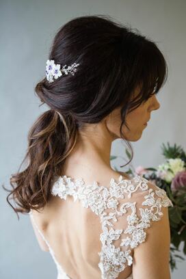 Violet comb white flowers with Swarovski crystal culture centres and little braces of crystals and pearls in brunette wedding hair style